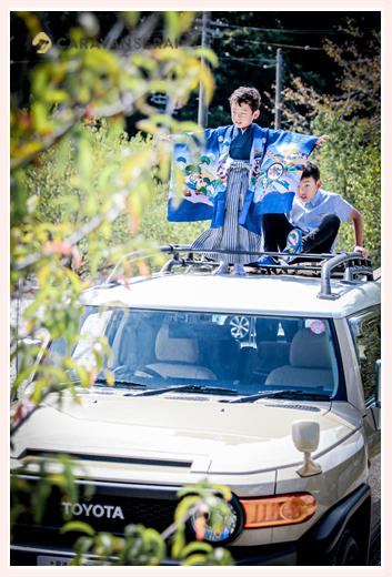 トヨタSUVの屋根上で記念写真 男の子二人