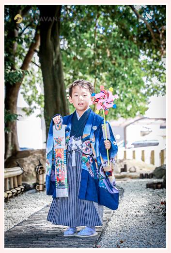 5歳の男の子の七五三 神社からもらった千歳飴と風車を持ってポーズ
