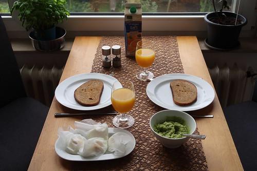 Pochierte Eier auf geröstetem und mit Avocadocreme bestrichenen Roggenmischbrot (Tischbild)
