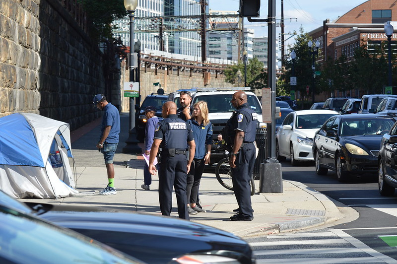 MPD officers and a city employee stand on a street corner while another man approaches a tent.