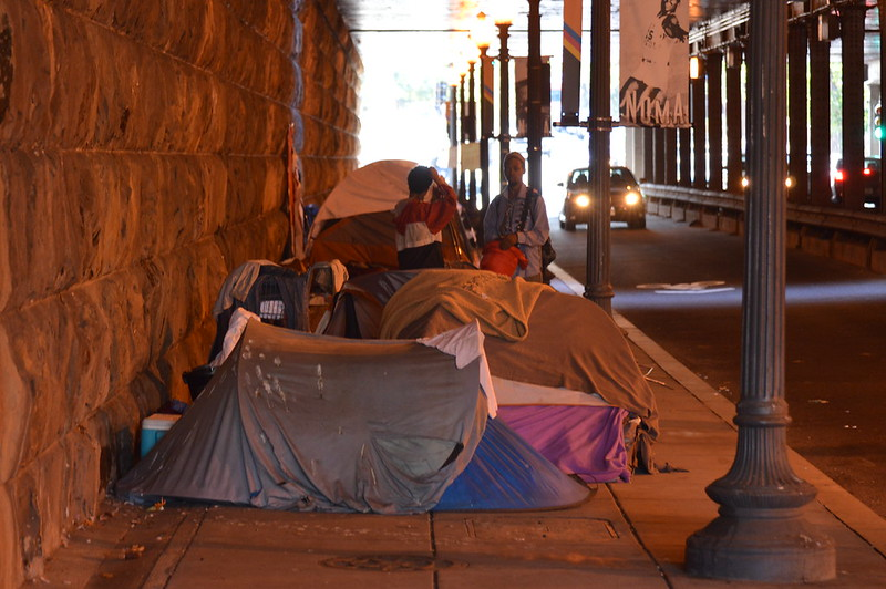 Tents lined up on the sidewalk in an underpass as one car drives by.