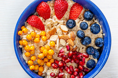 The concept of a healthy Breakfast-oatmeal with fruit and almonds | by wuestenigel