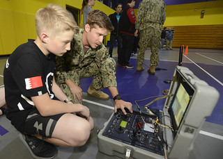 A Sailor assigned to Commander, Task Group 56.1, deployed to Naval Support Activity (NSA) Bahrain, shows a child how to operate an explosive ordnance disposal remote-controlled robot.