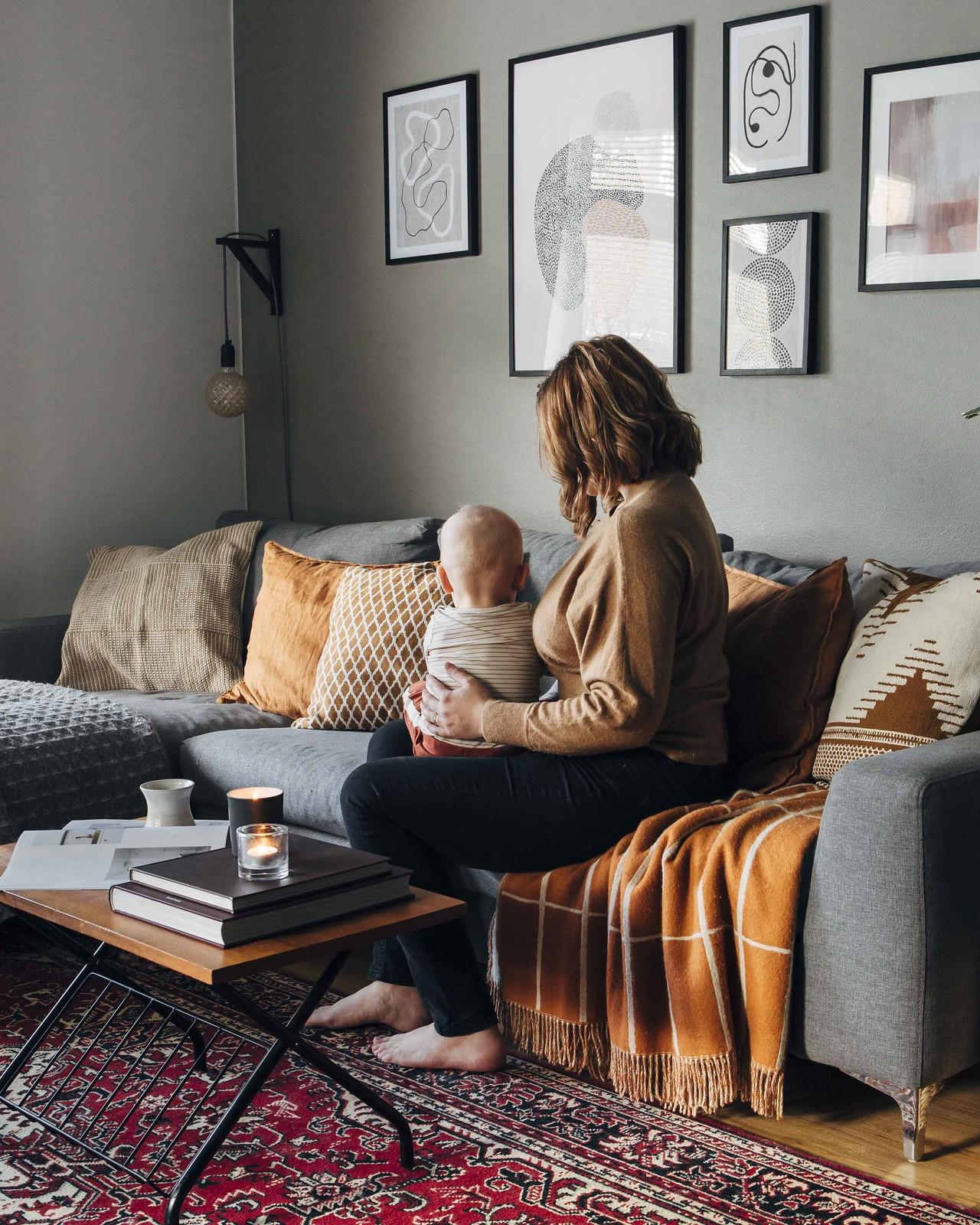 Nainen istuu harmaalla sohvalla lapsi sylissään.
