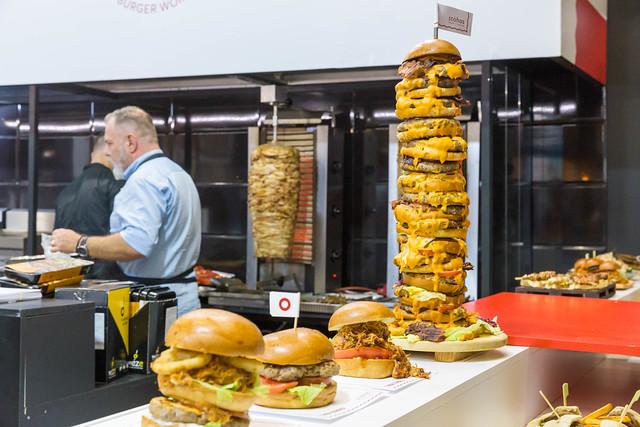 Fast-food - unterschiedliche Burger, ein Riesen Burgerturm und ein Dönerspieß im Hintergrund
