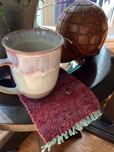 Coffee cup on handspun weft mug rug woven by irieknit on side table with carved wood turtle and zinc planter