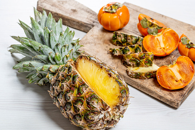 Fresh persimmon and pineapple fruit sliced on an old kitchen Board