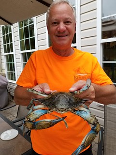 Photo of man holding a blue crab caught recently.