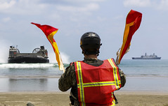 Construction Mechanic Constructionman Apprentice Caden Hans signals to a landing craft, air cushion (LCAC) as it approaches the beach after launching from USS Green Bay (LPD 20) off the coast of Malaysia during exercise Tiger Strike. (U.S. Navy/MC2 Anaid Banuelos Rodriguez)