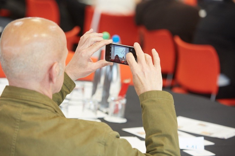Event attendee sitting at table taking a photo on his phone