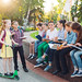 Happy Schoolmates Portrait. Schoolmates seating with books in a wooden bench in a city park and studying on sunny day.