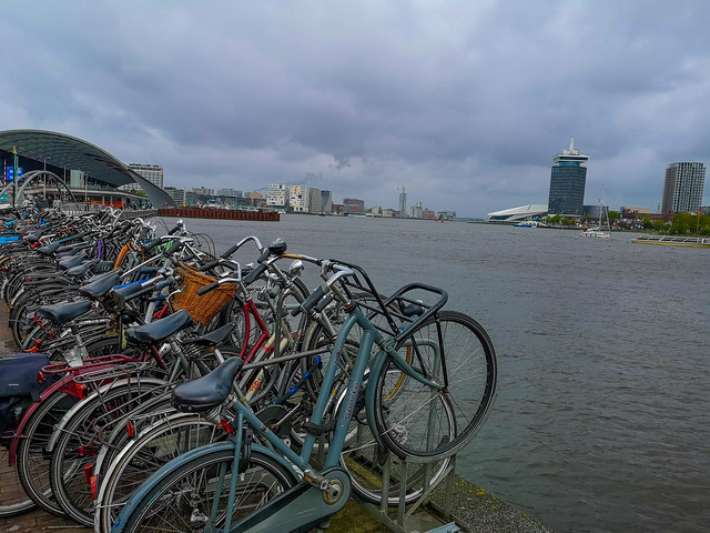 World renowned sight. Bicycles park and lined up sideward along the river IJ in Amsterdam.