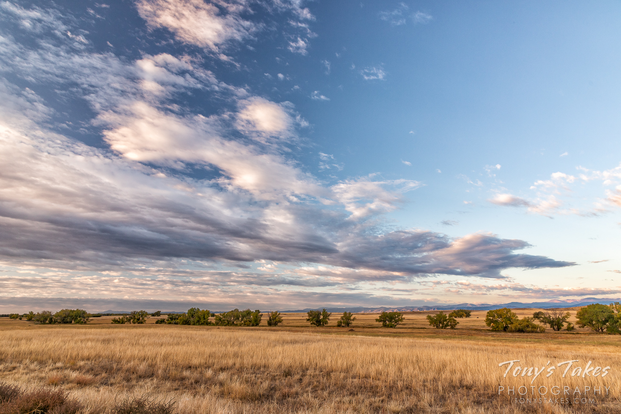 The early morning lights up the plains of Colorado to the Rocky Mountains. (© Tony's Takes)