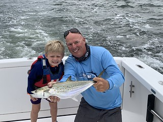 Photo of boy and man holding a Spanish mackerel