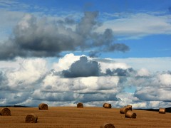 Clouds over harvested field with straw bales (2)