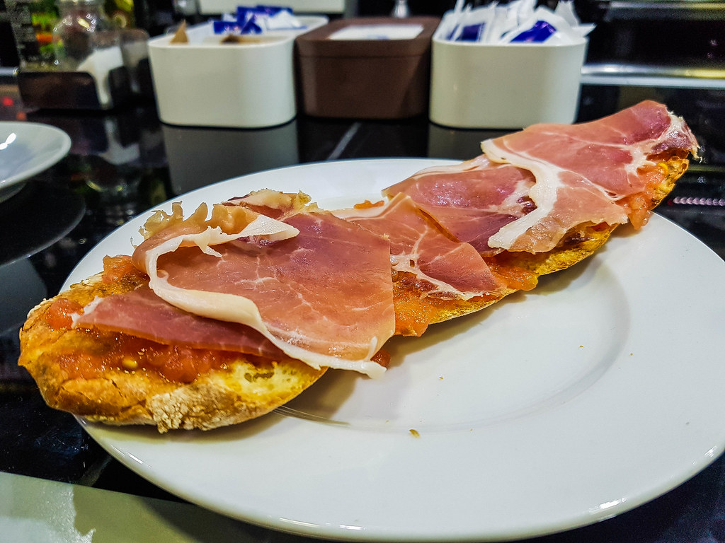 A slice of long, crusty bread, topped with grated tomatoes and slices of red jamon serrano