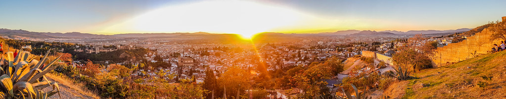 The sun is in the middle, setting, glaring and orange light over the city below. It's a panoramic photo
