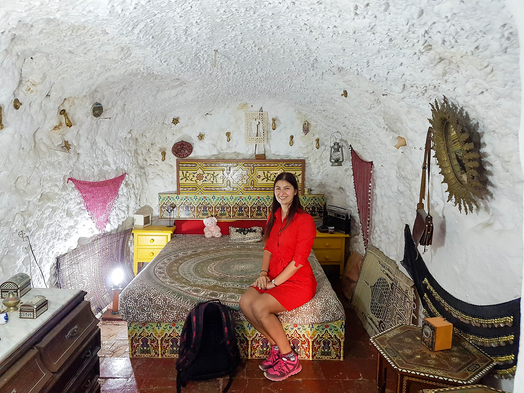 A photo of me wearing a red dress, sitting on the side of a bed inside a cave house. The room has white walls with lots of small decorations hanging off them