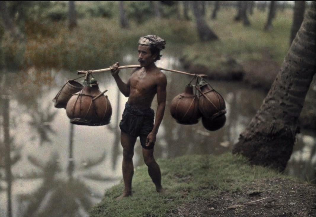 1928. Балиец несёт глиняные горшки с местным алкогольным напитком на продажу