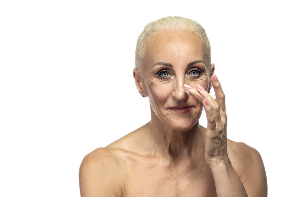 Senior Female People Concepts. Portrait Nude of  Senior Caucasian Woman Using Facial Cream. Against White Background.