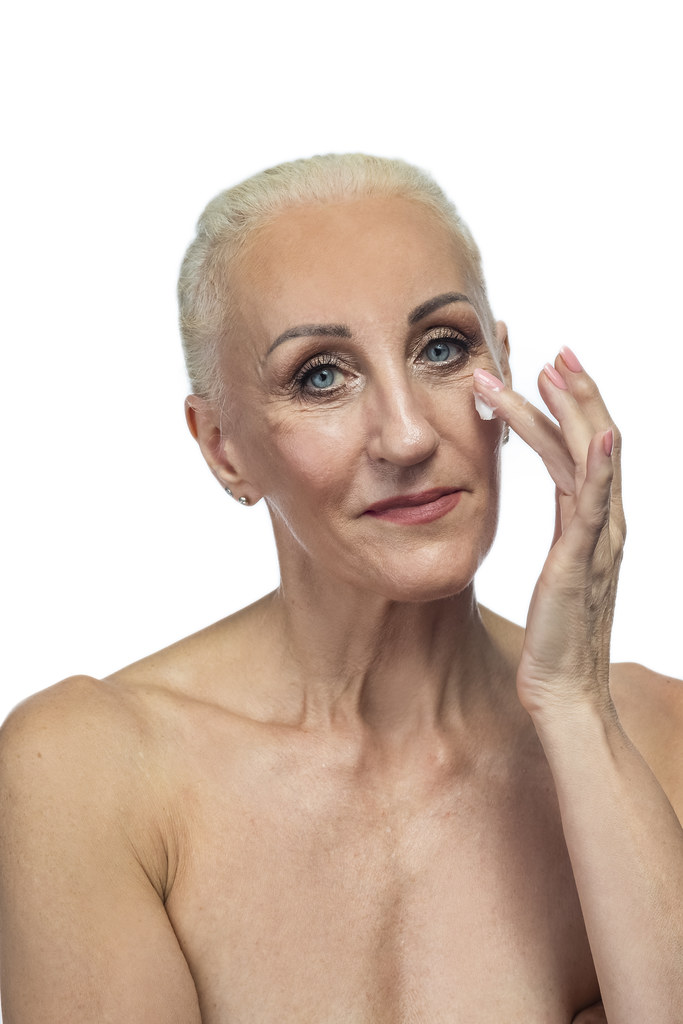 Senior Female Concepts. Portrait Nude of  Senior Caucasian Woman Using Facial Cream. Against White Background.
