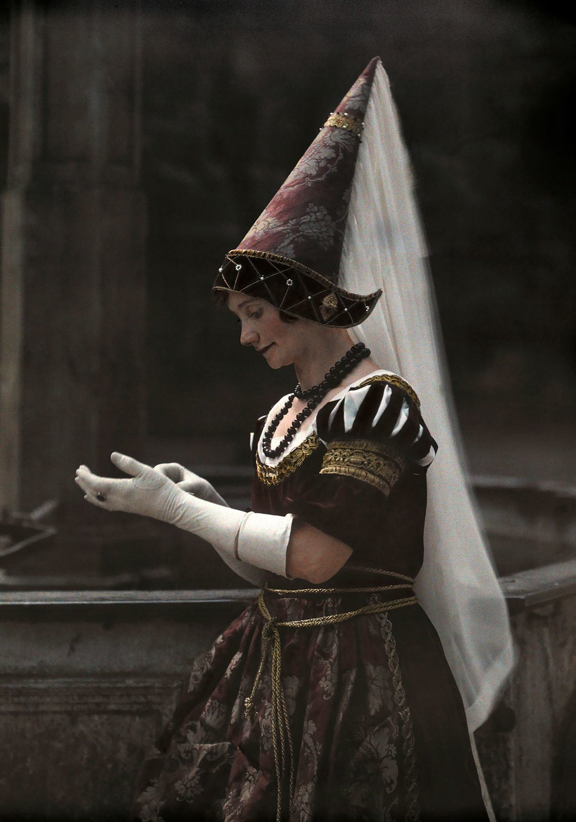 Женщина в остроконечной шляпе-хеннине с вуалью, поправляющая перчатки