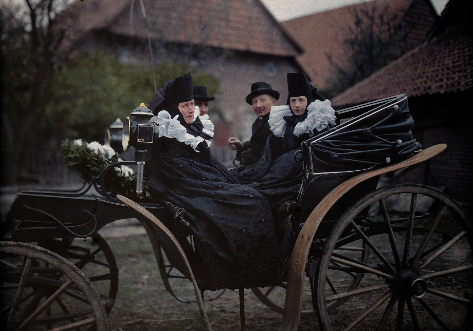 Скорбящие в традиционной траурной одежде садятся в коляску по дороге на похороны.