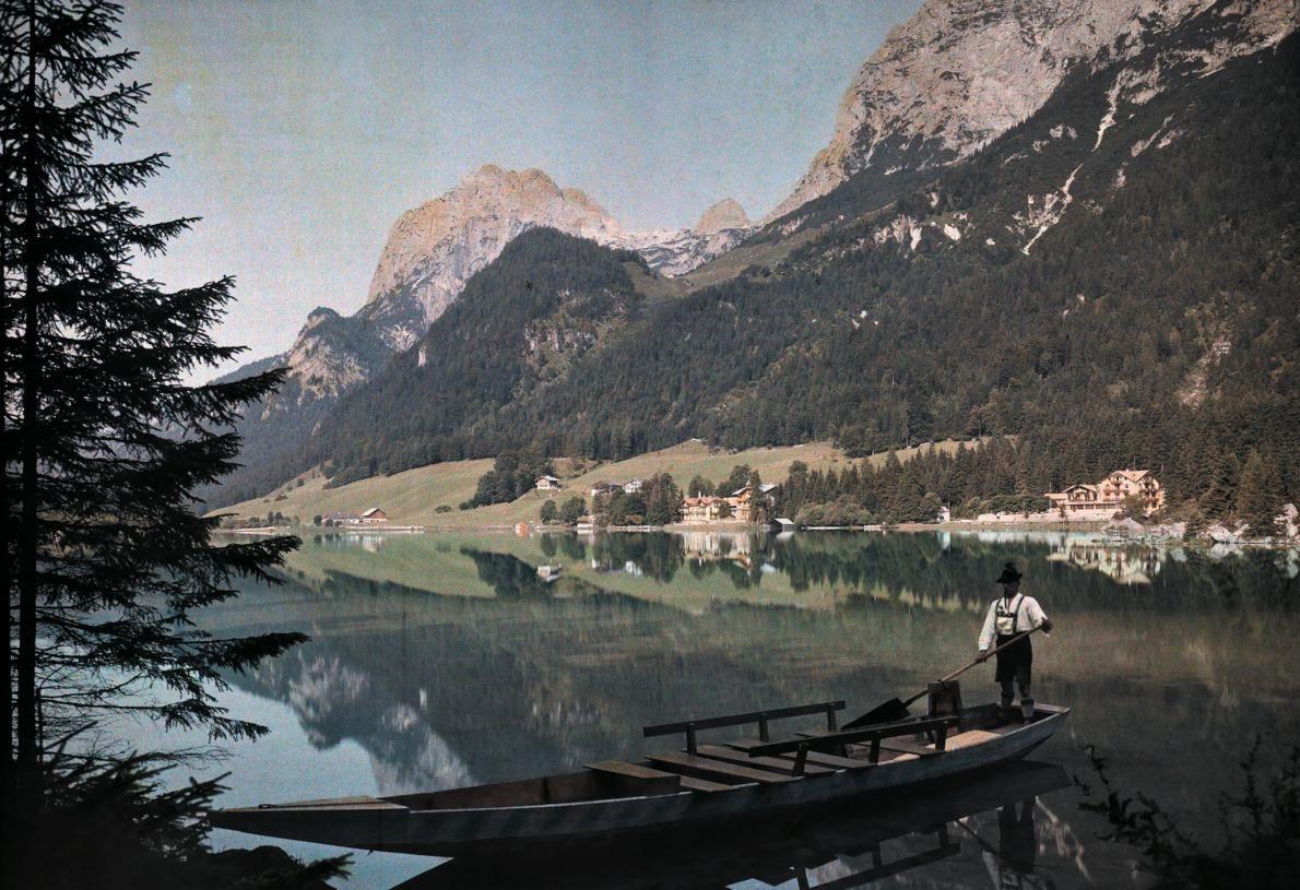 Мужчина в традиционном баварском наряде, плывущий в лодке по озеру Хинтерзе, Германия