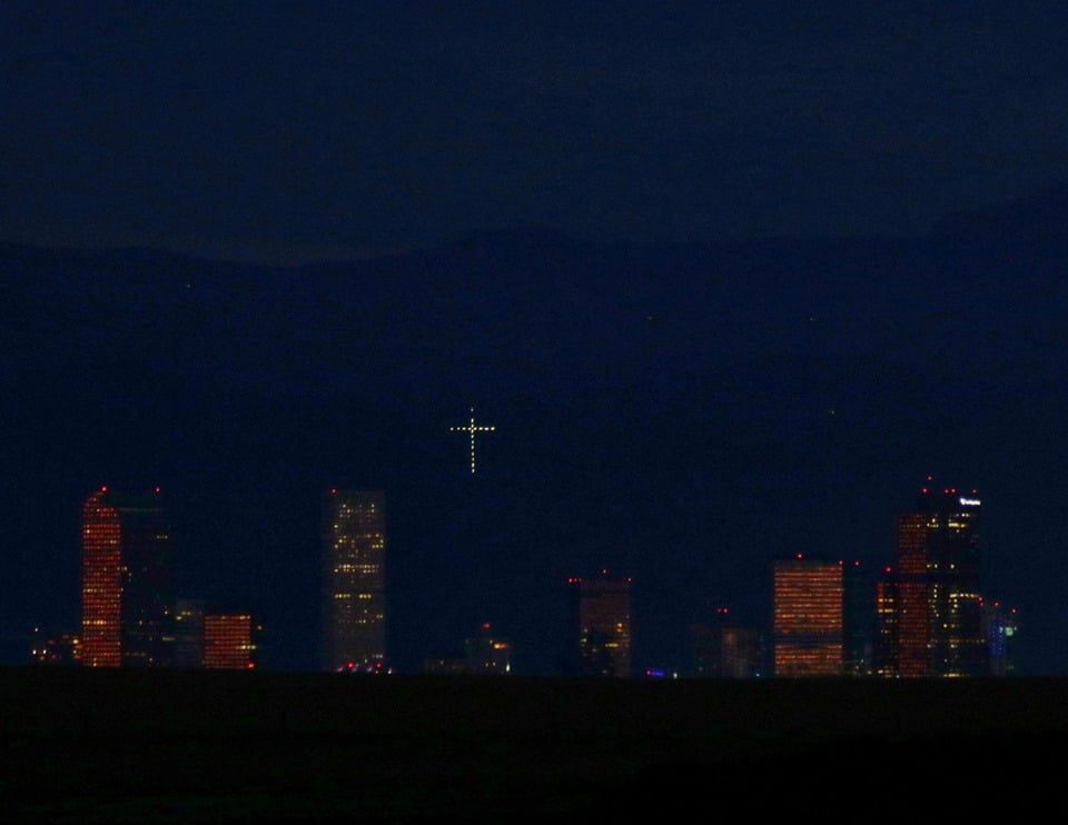 The Mount Lindo cross glows over the city of Denver at twilight. (Bill Hutchinson)