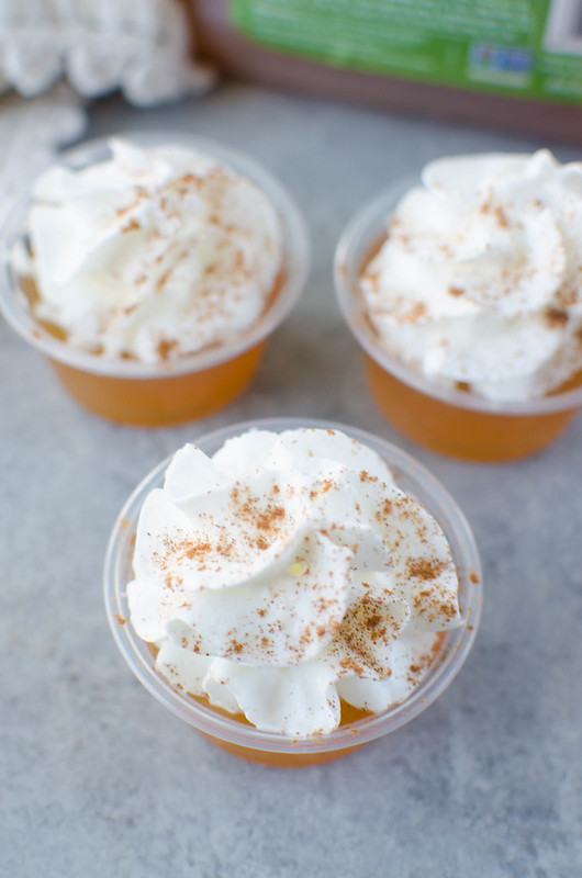 Apple Cider Jello Shots - perfect for fall parties! Apple cider and Fireball jello shots topped with whipped cream and a sprinkle of cinnamon.
