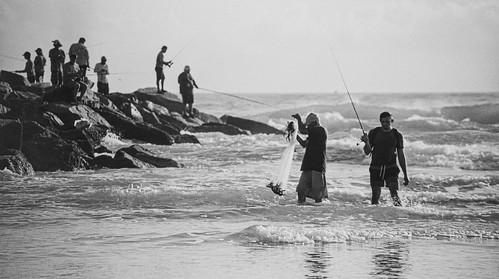 nikonf2 tamronsp80210mmf384cf 35mmfilm analog rollfilm slr blackandwhitenegativefilm kentmere100 googlenikcollection silverefexpro sammysantiago samuelsantiago fineartphotography walldecor smyrnadunespark newsmyrnabeach florida fishing fishermen sea waves rocks