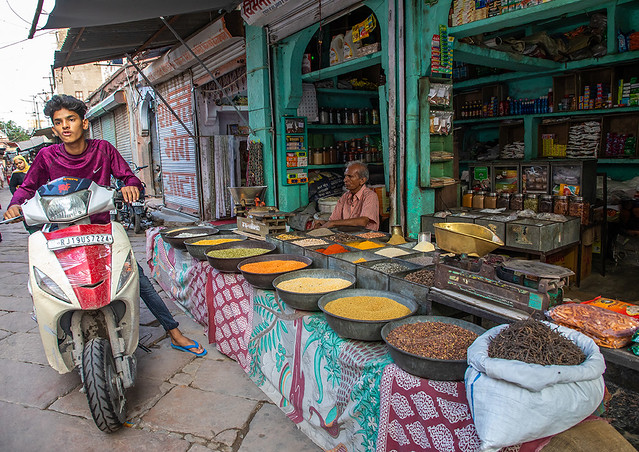 Indian man on a scooter passing by a shop selling spices, Rajasthan, Jodhpur, India