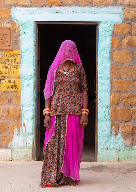 Portrait of a rajasthani woman hidding her face under a pink sari, Rajasthan, Jaisalmer, India