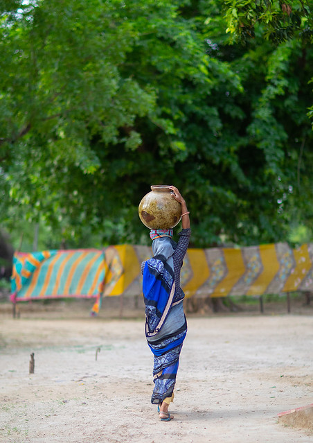 Indian woman carrying a jar on her head, Rajasthan, Baswa, India