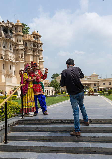 Indian tourists posing in traditional clothing in front of the facade of the city palace, Rajasthan, Udaipur, India