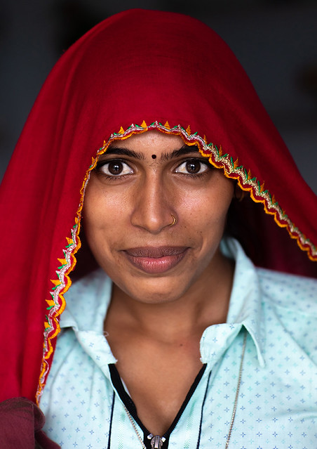 Portrait of a rajasthani woman in traditional red sari, Rajasthan, Baswa, India