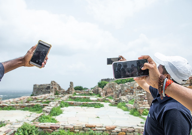 Tourists taking selfies in front of the ruined rana kumbha palace inside Chittorgarh fort complex, Rajasthan, Chittorgarh, India