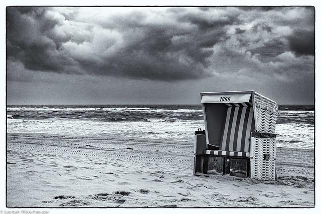 Einsamer Strandkorb in Sturm und Regen