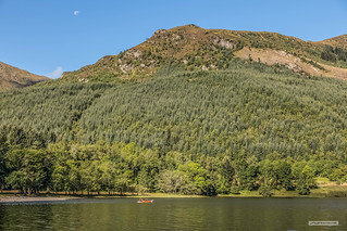 Kayaking on Loch Lubnaig under hills forest and a Quarter Moon.
