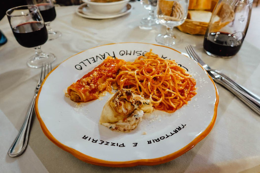A plate of red colored food: spaghetti, canelonni and some seafood.