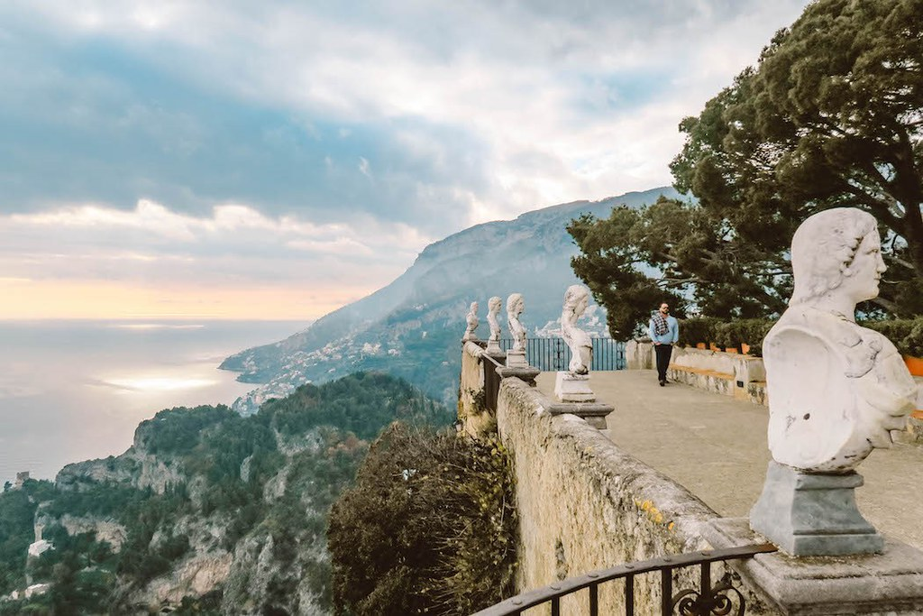 A garden built on a cliff, with statues on the stone walls. The view behing is of high cliffs and the sea
