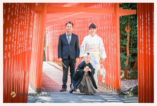 5歳の男の子の七五三 黒の羽織袴 神社の赤い鳥居の下で
