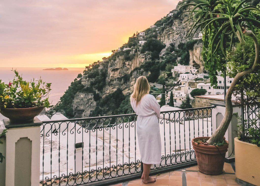 Admiring the sunset from the terrace of the hotel, looking over the cliffs. The sky is red and yellow.