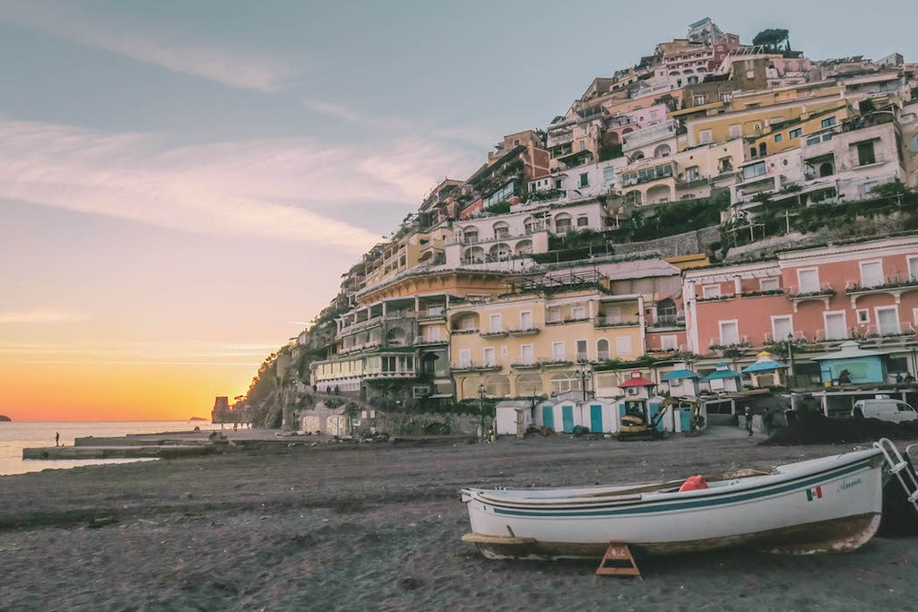 A boat on a the beach, behind it there are yellow, ored and orange houses built on the rocks. The sky is yellow because of the sunset