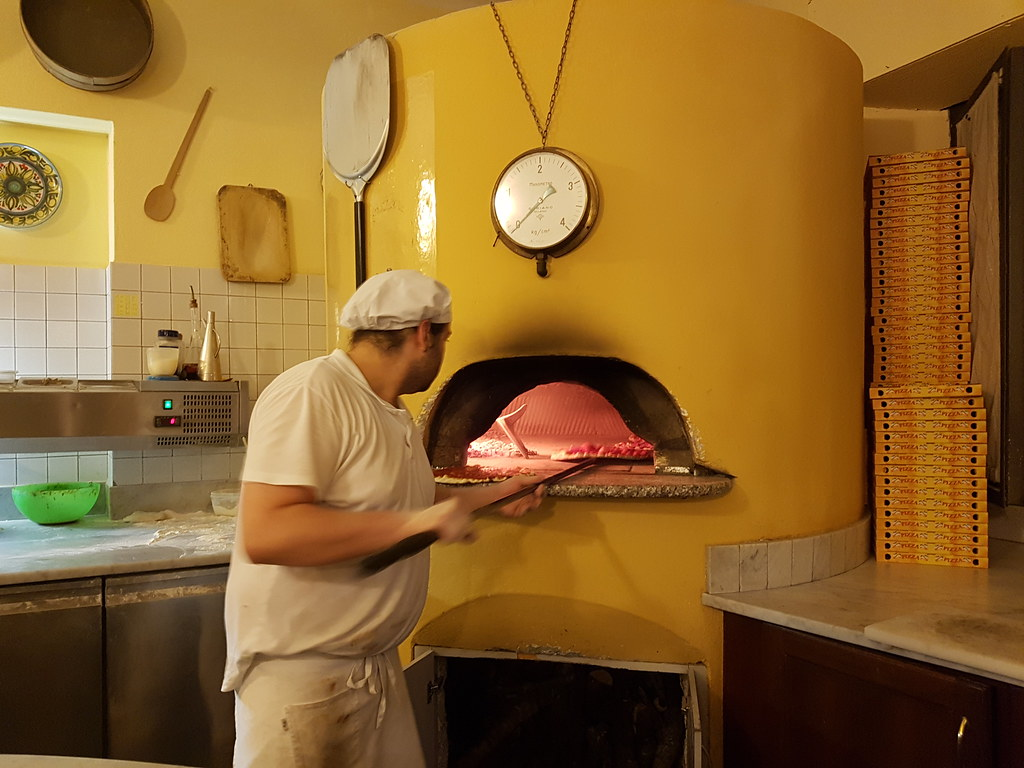 A man taking a pizza out from a traditional wooden oven