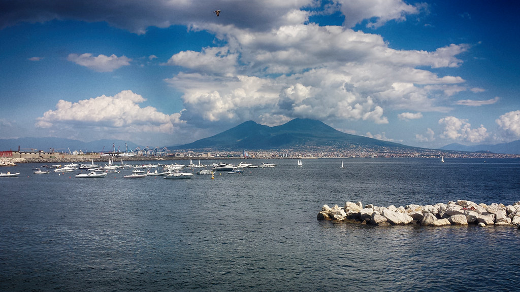 Vesuvius volcano seen from the harbour, with the sea in front and boats in the foreground