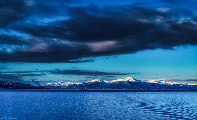 Panoramic view of the mountains and landscape aboard the Viking Sky cruise ship sailing on Ofotfjord and arriving at Narvik, Norway with a tanker in the distance under angry clouds-11a
