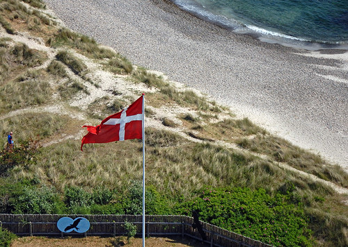 View of a Danish flag and the beach from the Lighthouse at Skagen in Denmark