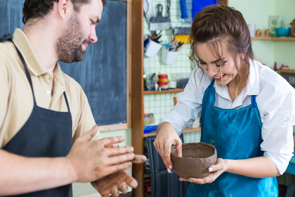 Claymaking Process Concept. Two Cheerful Professional Ceramists During a Process of Clay Preparation on Tables in Workshop.