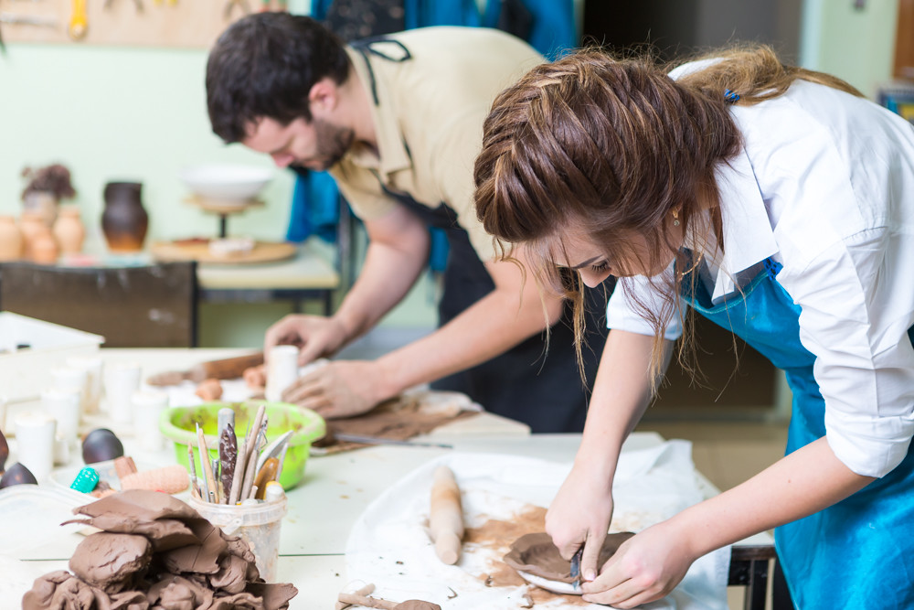 Pottering Concept. Professional Ceramists or Claymakers During a Process of Clay Preparation on Tables in Workshop.